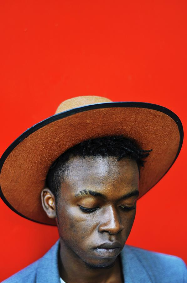 Close-up Of Man Wearing Hat Against Red Photograph by Samson Wamalwa / Eyeem