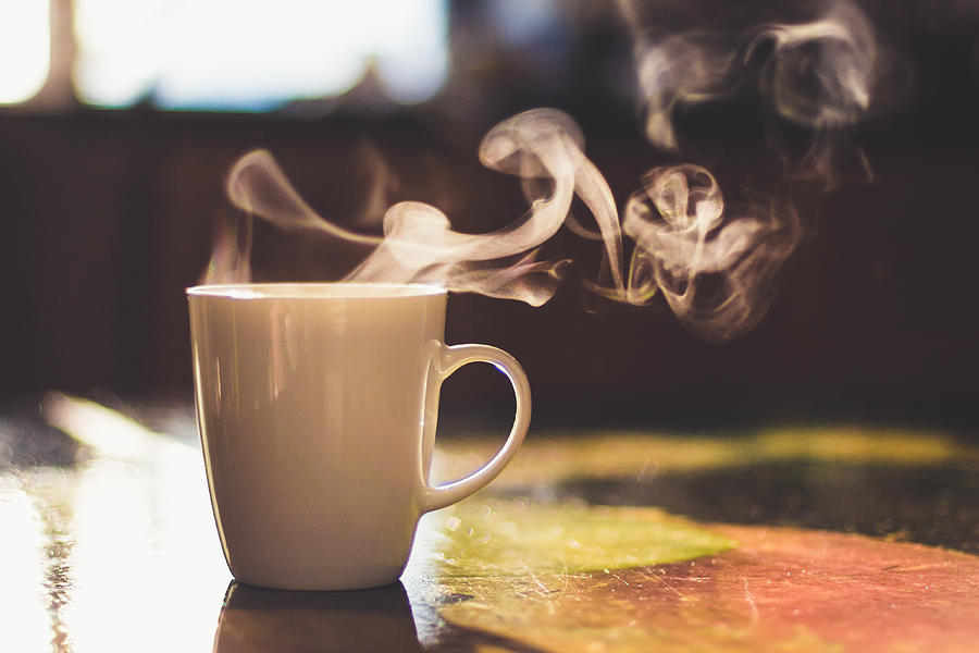 Close up of steaming cup of coffee or tea on vintage table - early morning breakfast on rustic background Photograph by Alina Rosanova