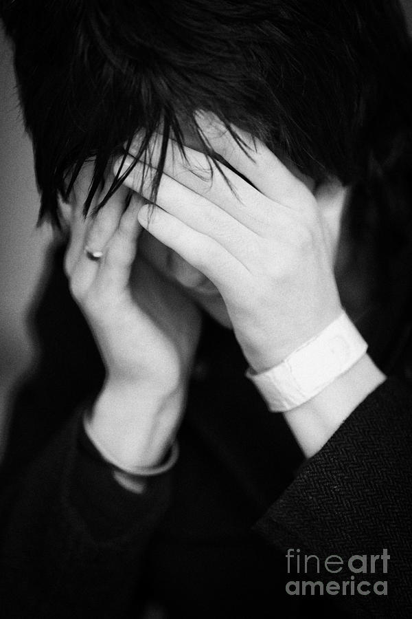 Northern Ireland Photograph - Close Up Of Young Dark Haired Teenage Man Sitting With His Head In His Hands Hiding His Face Staring by Joe Fox