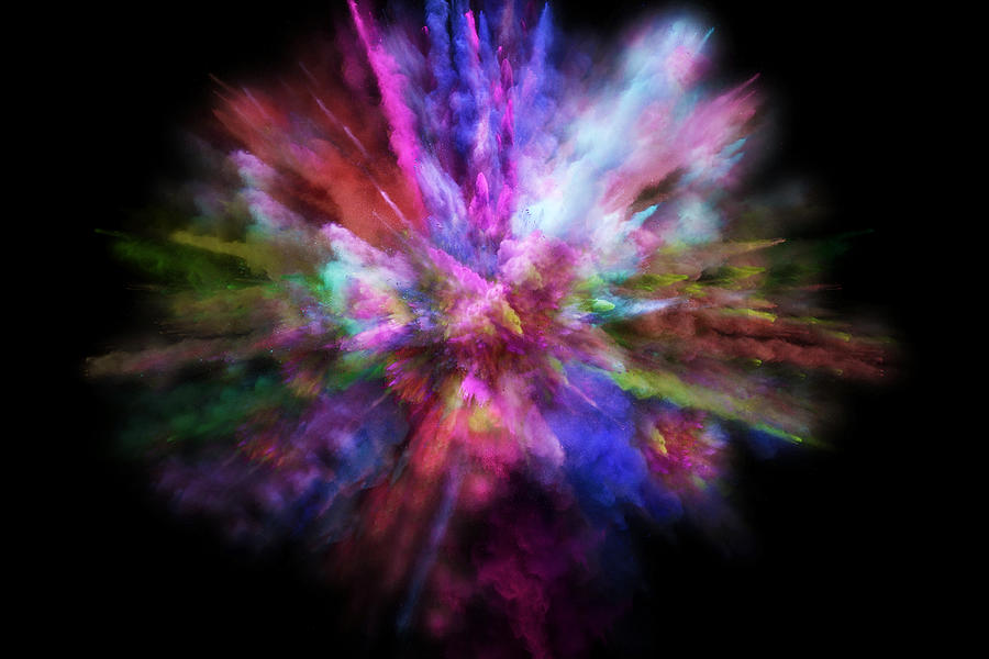 Colorful powder explosion in all directions in a nice composition with vivid colors and black background. Photograph by Artur Debat