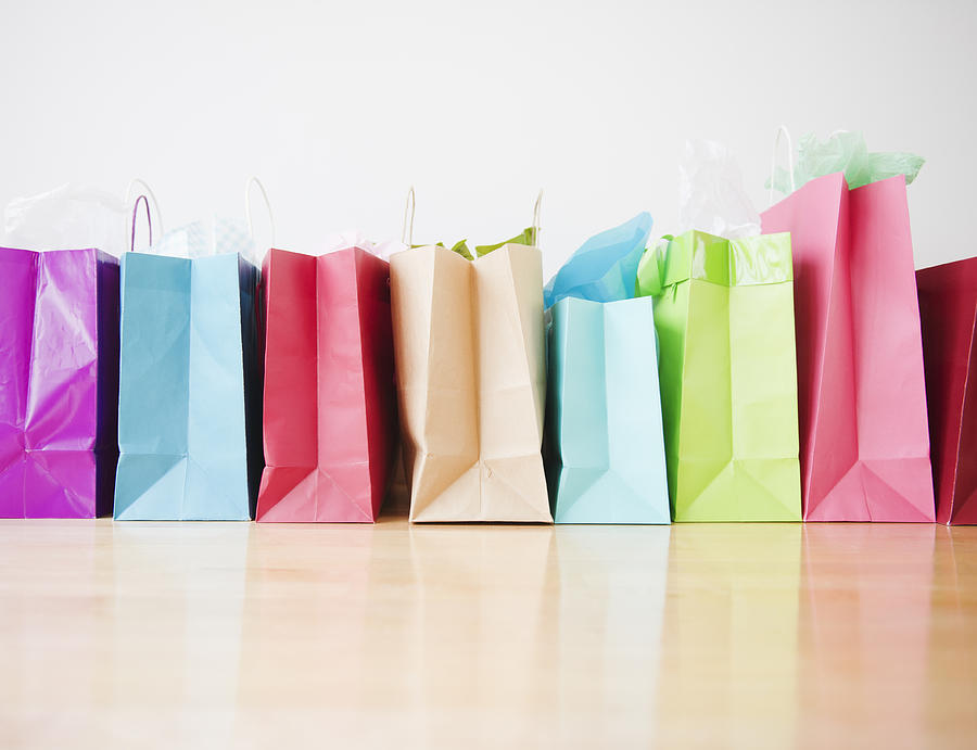 Colorful shopping bags standing in row Photograph by Jamie Grill