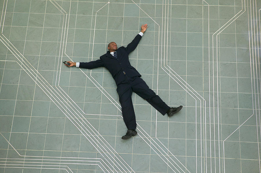 Conceptual Shot Of An African American Business Man As He Lays Flat On The Ground Holding His Phone Photograph by Photodisc