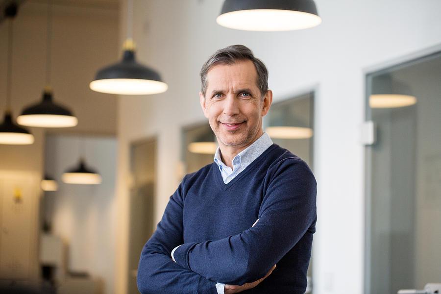 Confident mature businessman in office Photograph by Alvarez