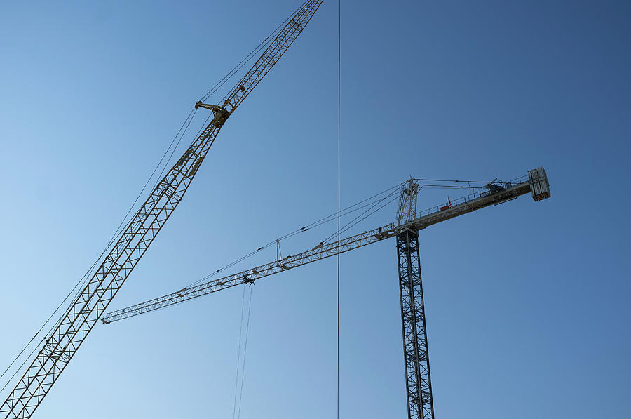 Construction Cranes Against A Blue Sky Photograph by Alvis Upitis