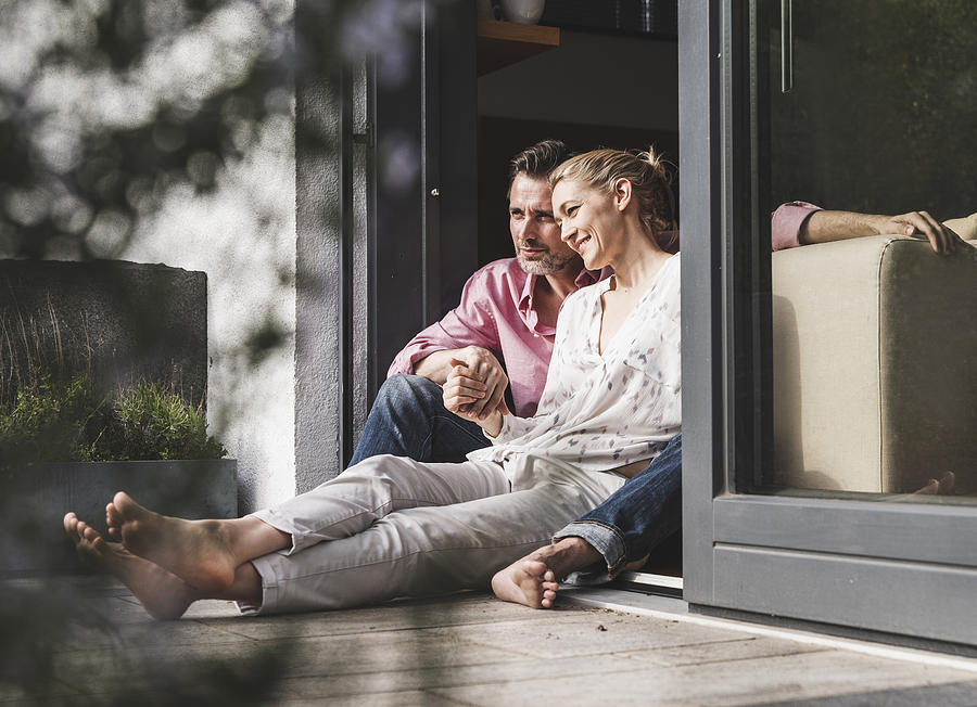 Content Mature Couple Relaxing Together At Open Terrace Door Photograph by Westend61