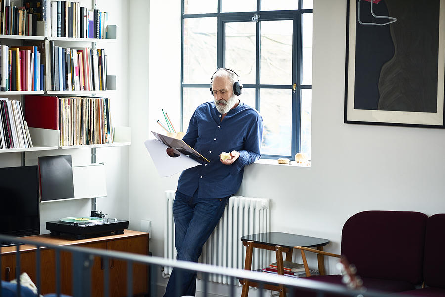 Cool looking senior man in apartment listening to vinyl record Photograph by 10000 Hours