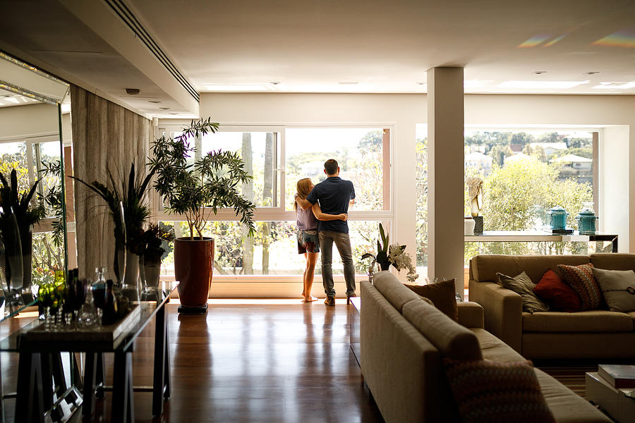Couple admiring the view from the living room of their house. Photograph by Capuski