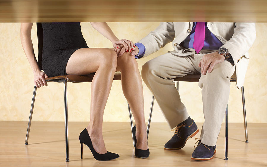 Couple Holding Hands Under The Table Photograph by Peter Dazeley