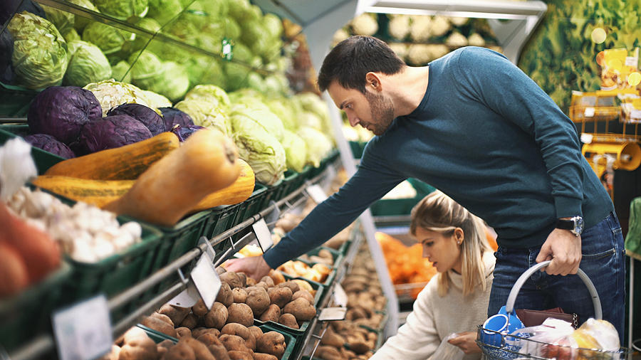 Couple in supermarket buying vegetables. Photograph by Gilaxia