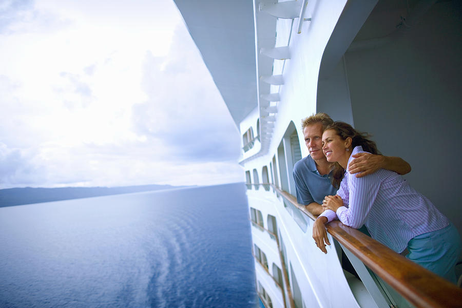 Couple leaning on rail of cruise ship, looking at ocean Photograph by David Sacks