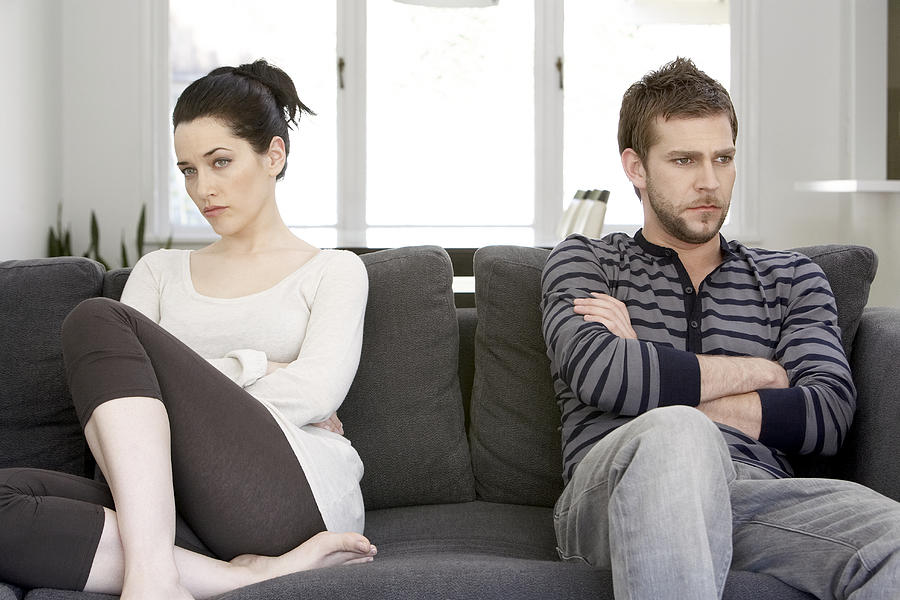 Couple sitting on sofa with arms folded, looking angry Photograph by Noel Hendrickson