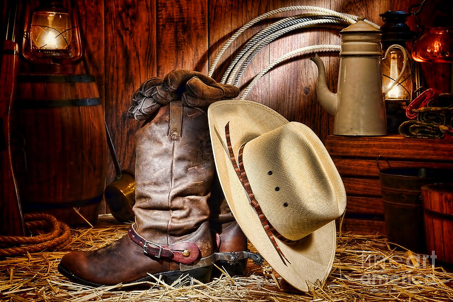 Cowboy Gear. American West rodeo cowboy traditional white straw hat resting  on leather working rancher roper boots with ... 31dd41e0d518