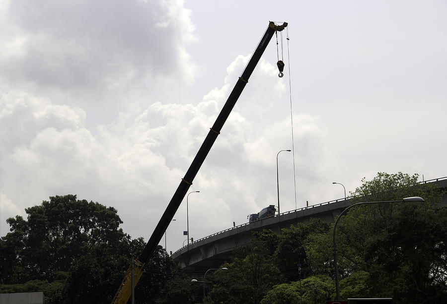Crane Lifting Up Some Machinery Next To A Flyover In Singapore