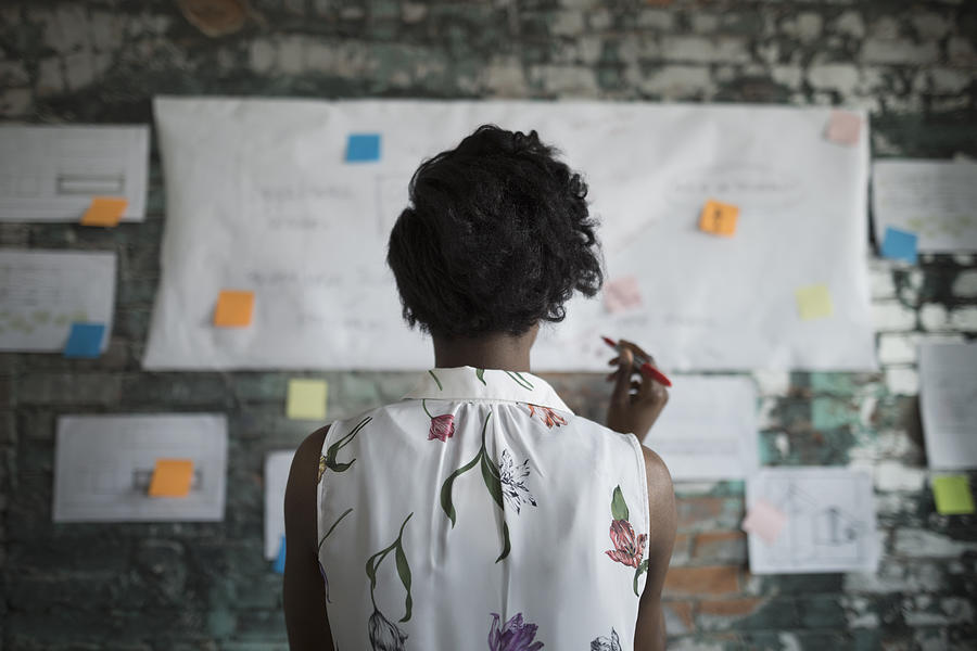 Creative Businesswoman Brainstorming, Reviewing Flow Chart Hanging On Brick Wall In Office Photograph by Hero Images