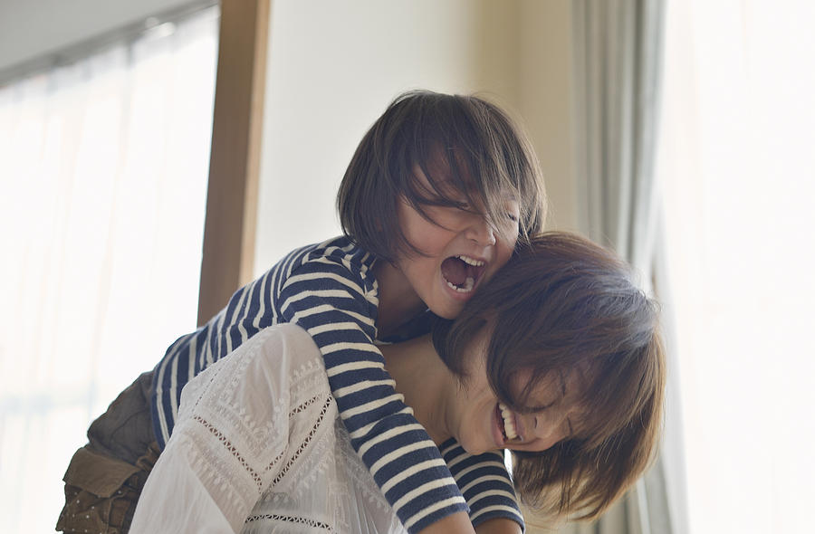 Daughter playing with Mother in the room Photograph by Yagi Studio