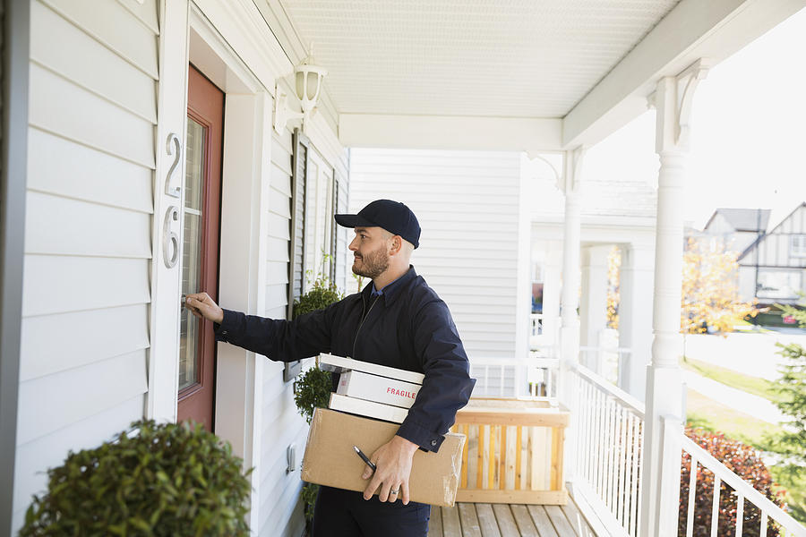 Delivery Man With Packages Knocking At Front Door Photograph by Hero Images