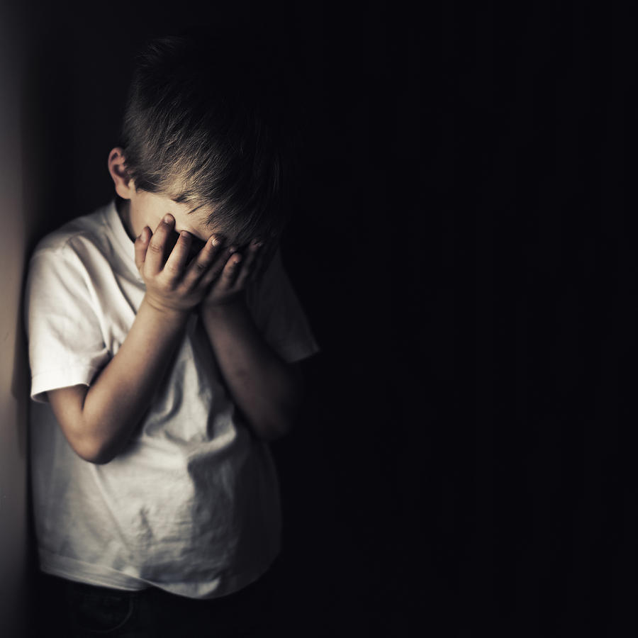 Depressed crying little boy holding head in hands Photograph by Imgorthand