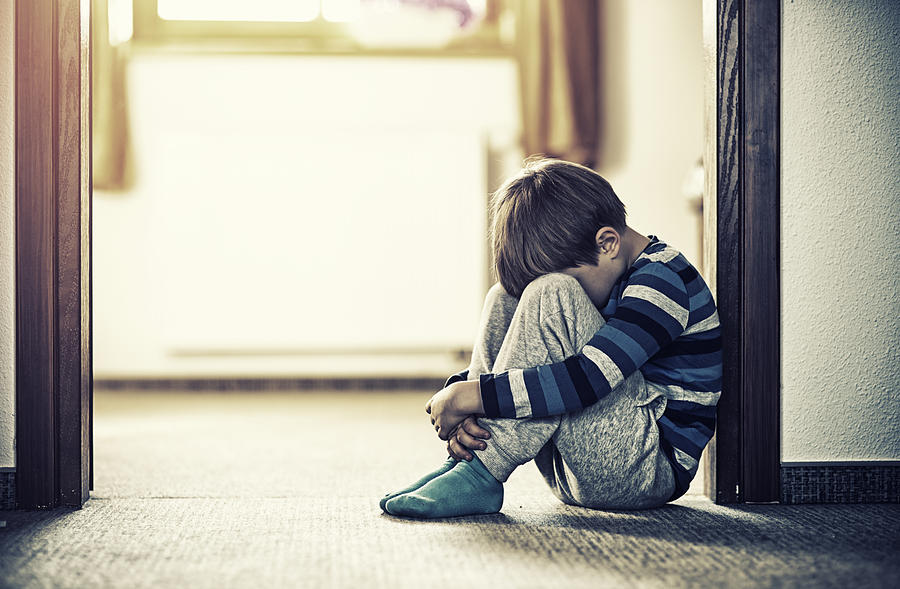 Depressed little boy sitting on the floor Photograph by Imgorthand