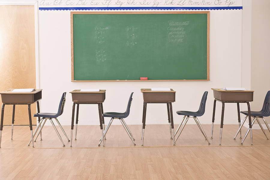 Desks In Row In Classroom by Comstock Images