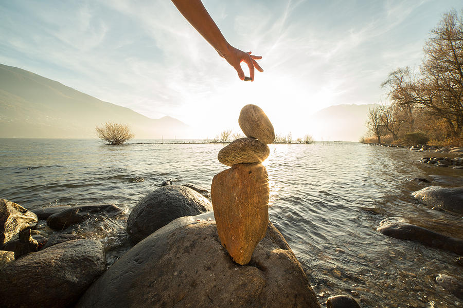 Detail of person stacking rocks by the lake Photograph by Swissmediavision