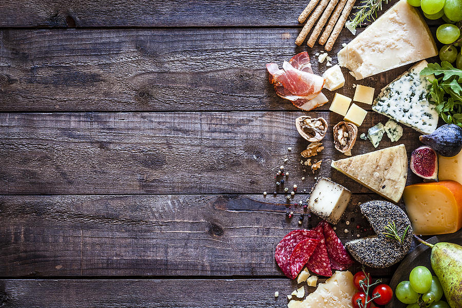 Different types of cheeses on rustic wood table Photograph by Fcafotodigital