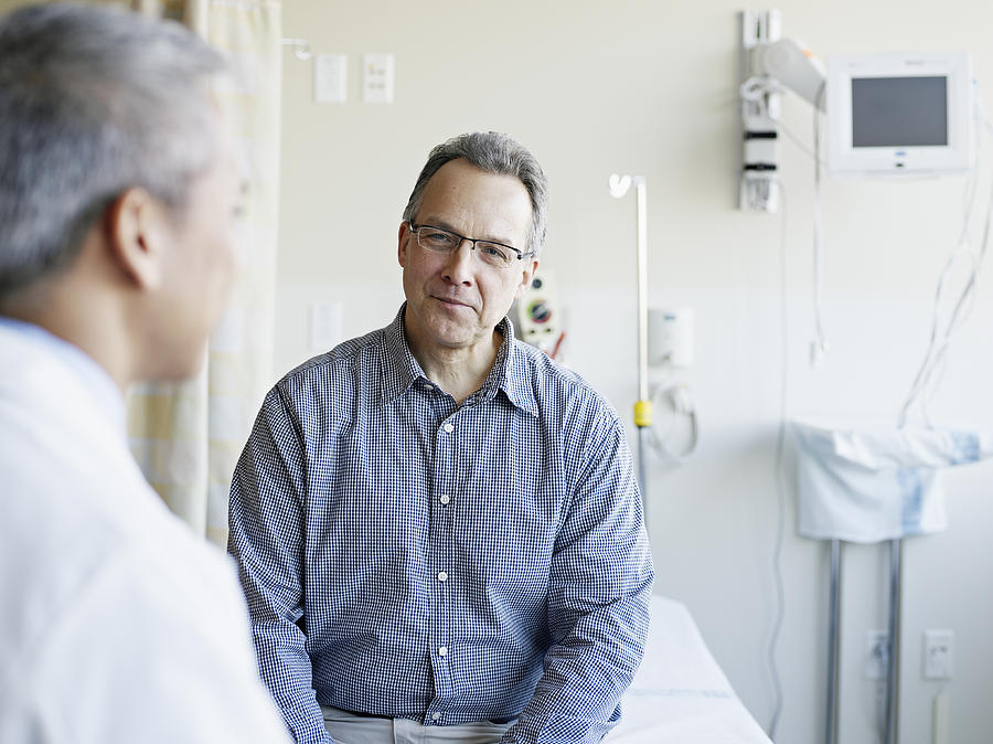Doctor talking to patient in hospital room Photograph by Thomas Barwick