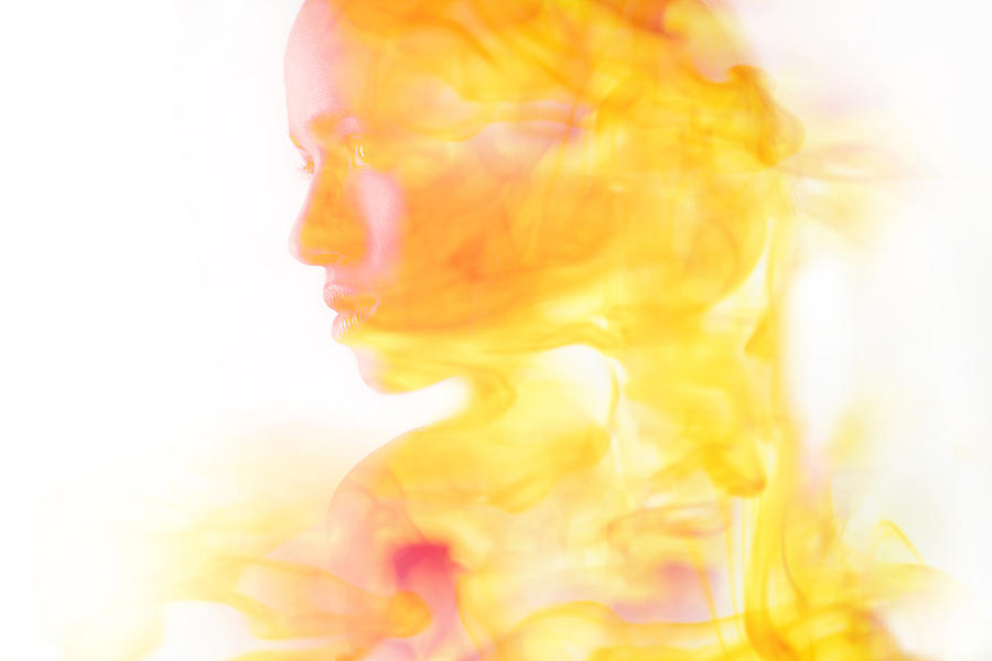 Double exposure of face of Mixed Race woman and fire Photograph by JGI/Tom Grill