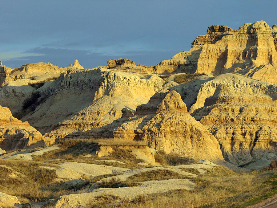 Badlands National Park South Dakota Sd Parks North America American Badland Landscape Landscapes Sandstone Sandy Formations Formation Bad Lands Sky Skies Dusk Neutral Beige Colors Rugged Beauty Scenic Scenery Hiking Travel Vacation Destinations Blue Rapid City Brown Lighting Light Dimensional Dimensions Photography Photos Artistic Art Unique Rocky Rock Rocks James Melissa Peterson Nature Outdoor Wilderness Adventure Wall Buttes Pinnacles Grass Prairie Southwestern Dynamic Golden Hour Unusual  Photograph - Dynamic Lighting by James Peterson