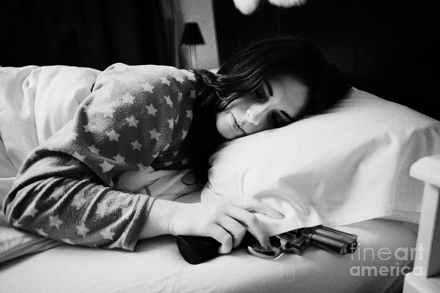 Table Photograph - Early Twenties Woman With Hand On Handgun Under Pillow At Night In Bed In A Bedroom by Joe Fox