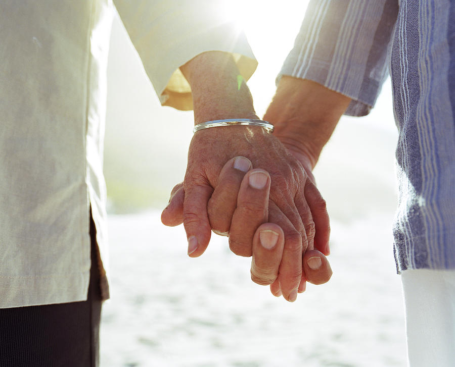 Elderly couple holding hands, close-up of hands Photograph by Bigshots