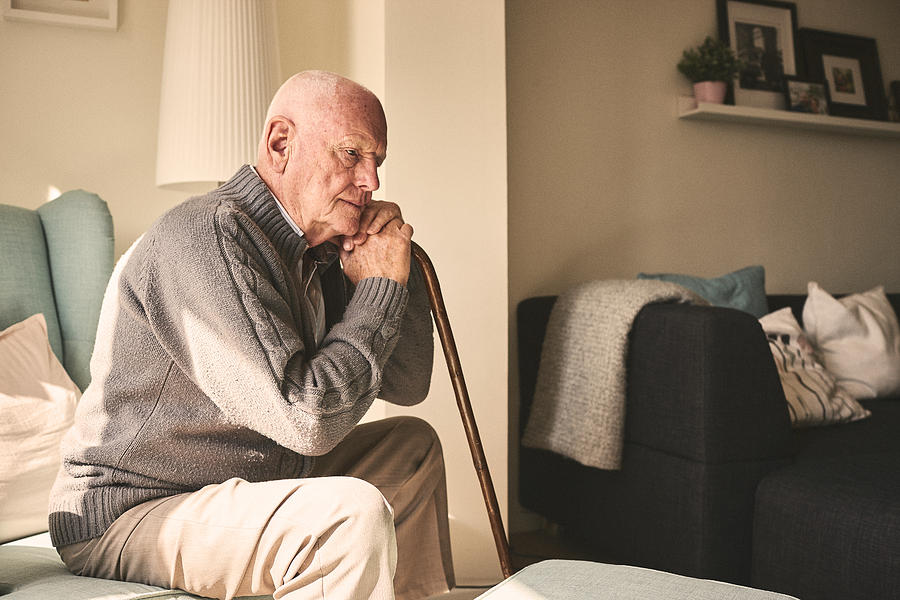 Elderly man sitting alone at home Photograph by Dean Mitchell