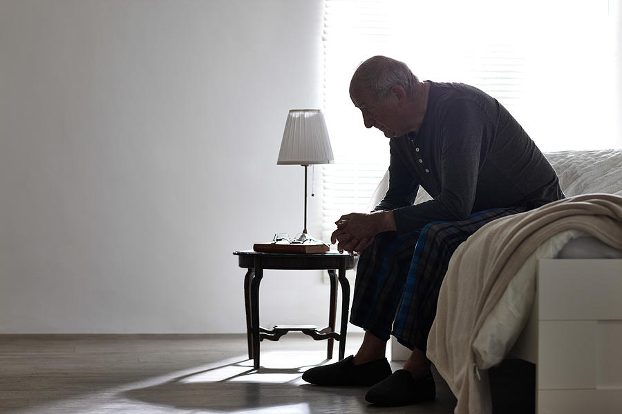 Elderly man sitting on bed looking serious Photograph by Dean Mitchell