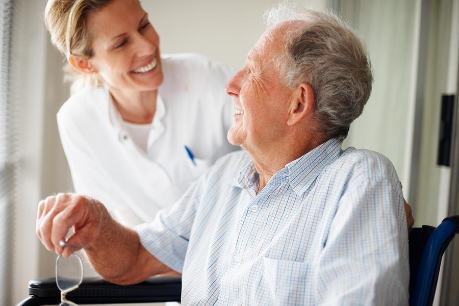 Elderly Man Speaking To A Nurse Photograph by Jacob Wackerhausen