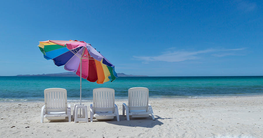 Empty Lounge Chairs And Umbrella At Beach Against Blue Sky Photograph by Jesse Coleman / EyeEm