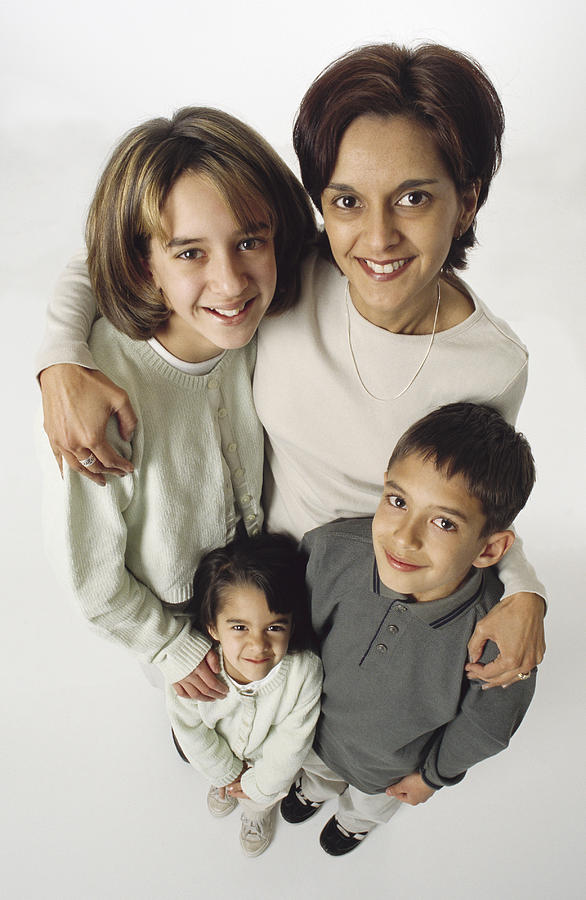 Ethnic Family Mom With Her Arms Around Her Three Young Kids Photograph by Photodisc
