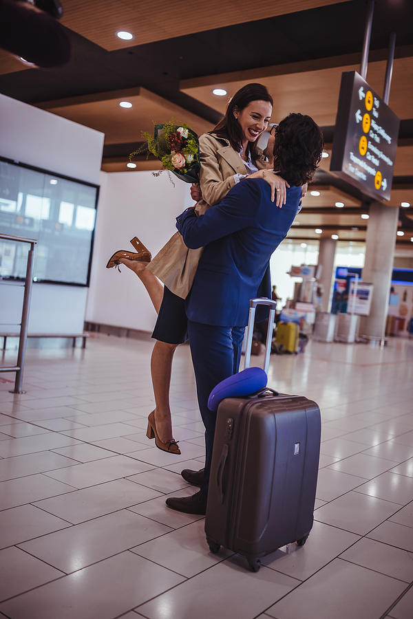Excited Young Man Welcoming Girlfriend With Flowers At Airport Photograph by Wundervisuals
