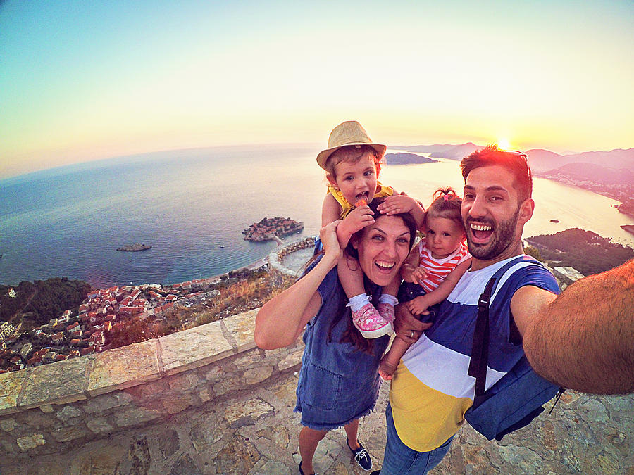 Family with two little daughters travel in nature, making selfie, smiling Photograph by gdinMika