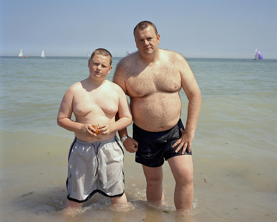 Father And Son (11-13) Standing In Sea, Portrait Photograph by Alan Powdrill