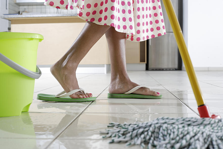 Feet of woman mopping kitchen Photograph by Peter Cade