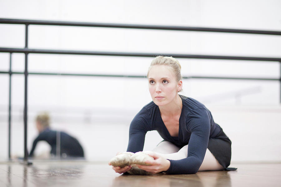 Female Ballerina Stretching On The Floor Photograph by Zero Creatives