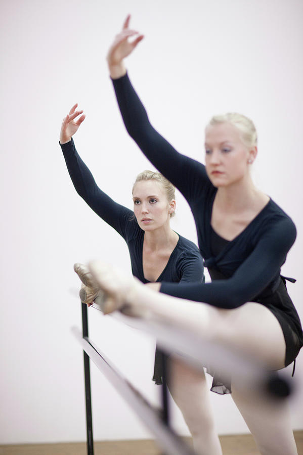 Female Ballerinas Stretching At The Photograph by Zero Creatives