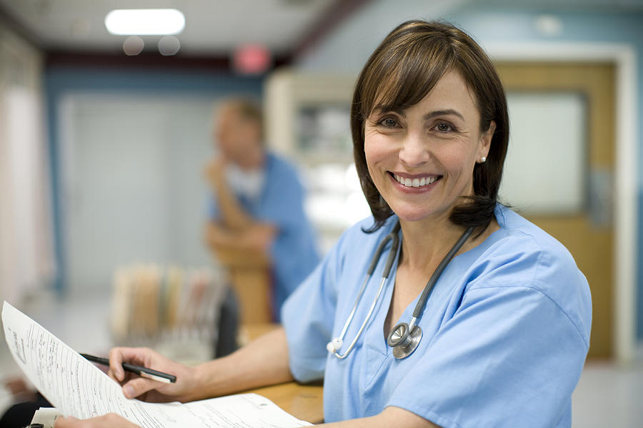 Female doctor holding medical records, smiling, portrait Photograph by Thomas Northcut