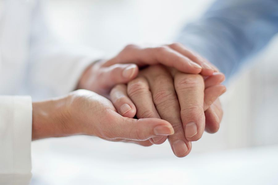 Female Doctor Holding Patient's Hand Photograph by Science Photo Library
