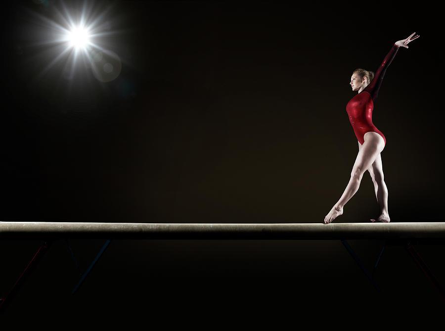 Female Gymnast Balancing On Beam Photograph by Mike Harrington