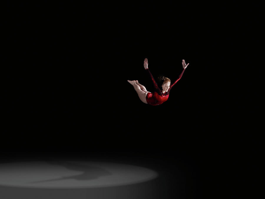 Female Gymnast Soaring Through Air Photograph by Mike Harrington