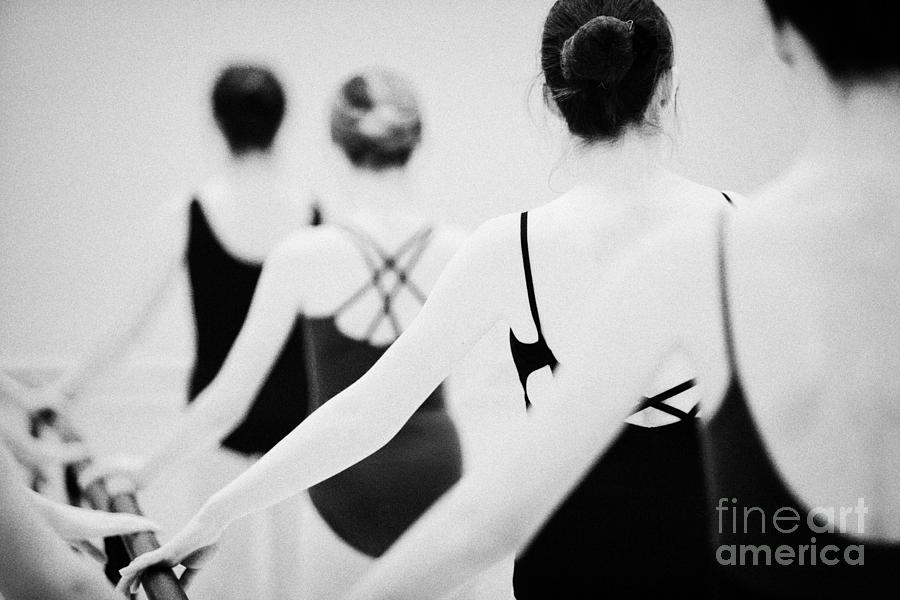 Ballet Photograph - Female Teenage Ballet Students Holding On To A Ballet Barre At A Ballet School In The Uk by Joe Fox