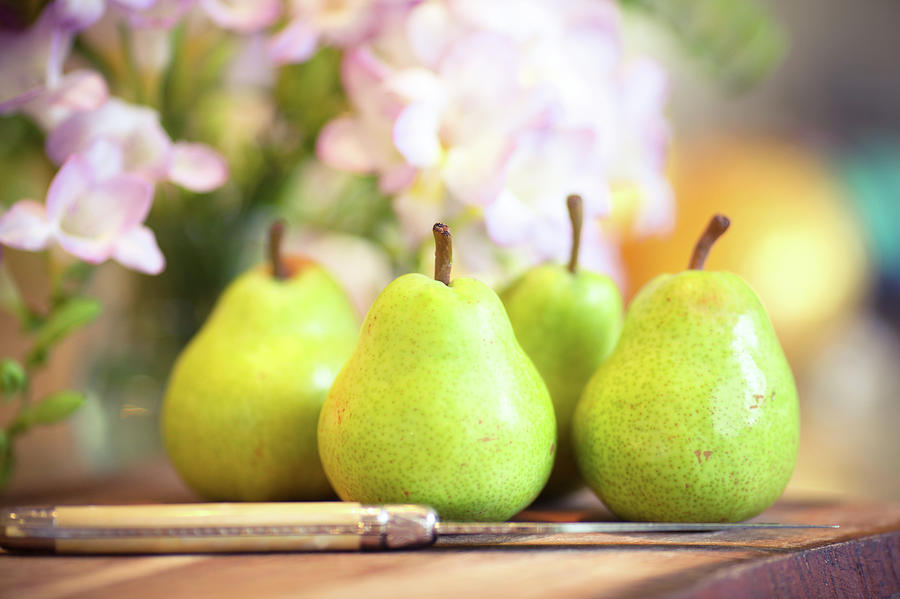 Four Green Pears On Wooden Board Photograph by Sasha Bell