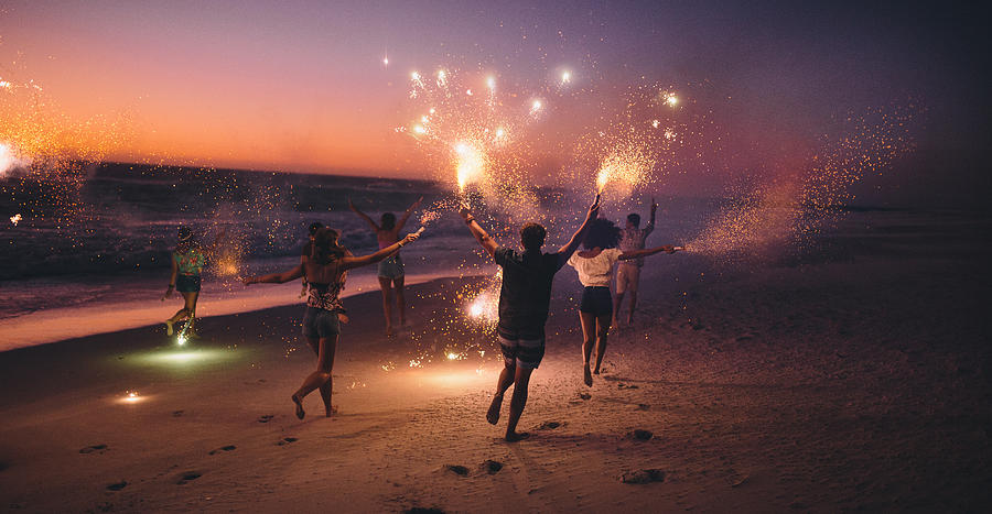 Friends running with fireworks on a beach after sunset Photograph by Wundervisuals