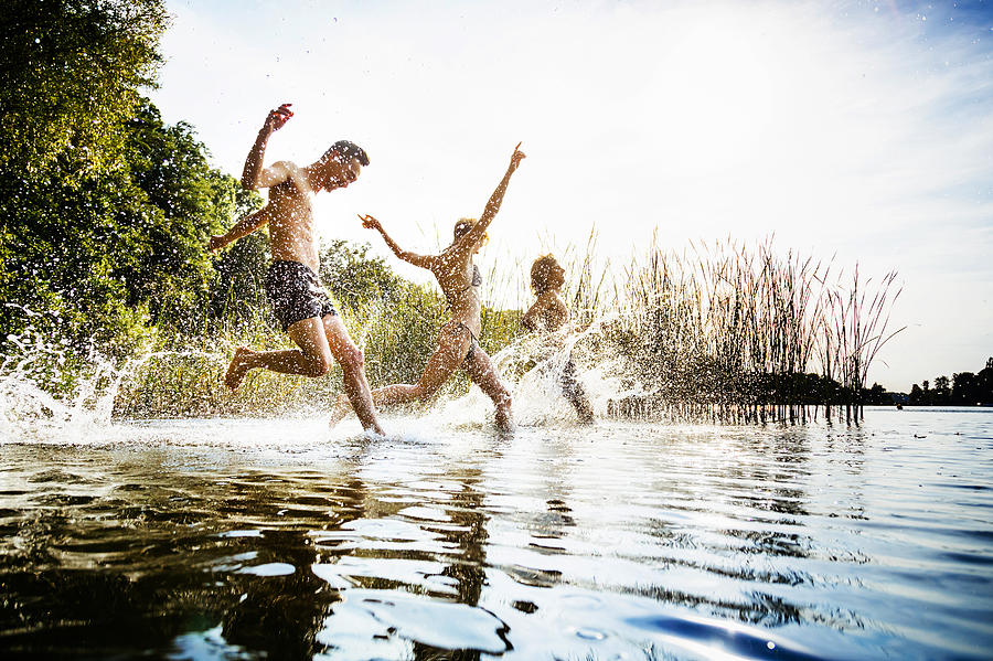 Friends Splashing In Water At Lake Together Photograph by TommL