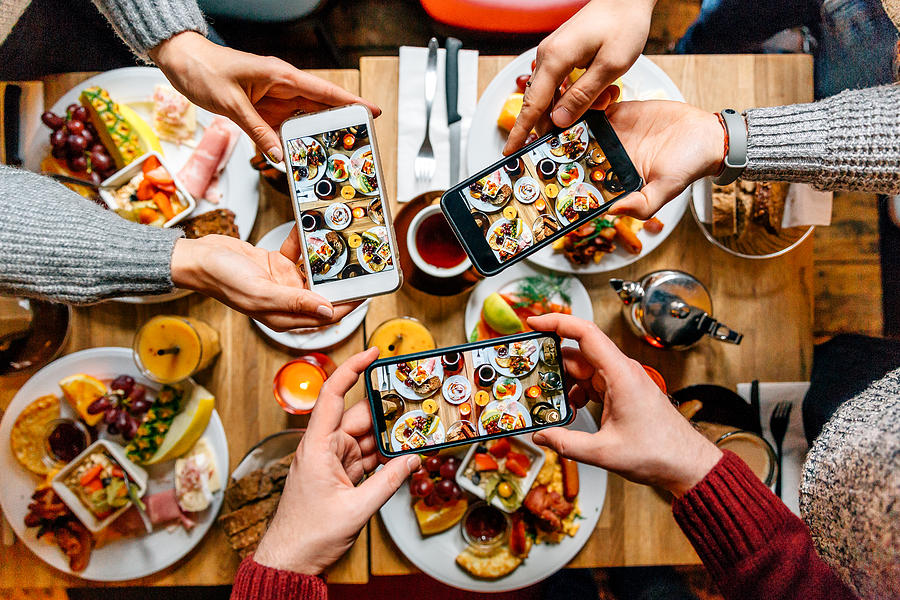 Friends taking pictures of food on the table with smartphones during brunch in restaurant Photograph by Alexander Spatari